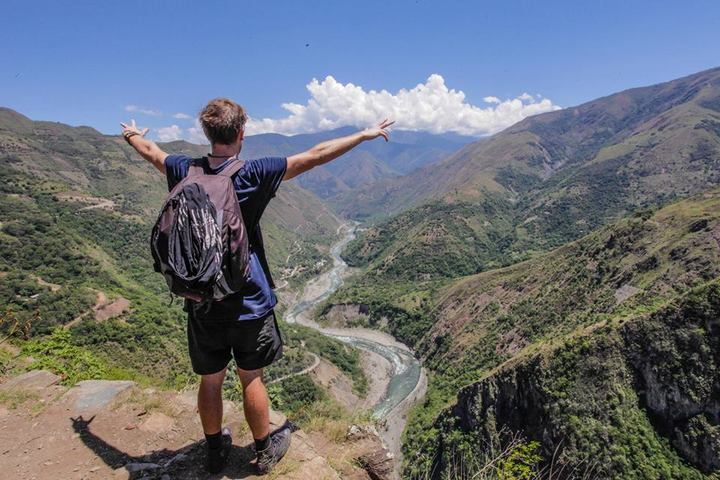 traveller with his arms up overlooking the sacred valley cusco peru tourism