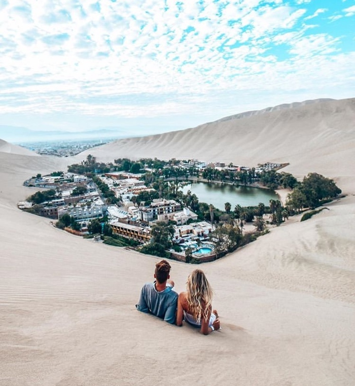 couple sitting in the sand dunes of huacachina peru peru hop discount code