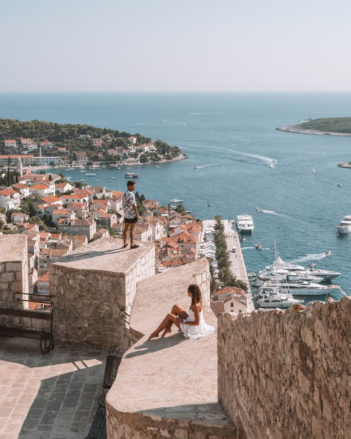 2 people standing on a ledge looking at the croatian sea and boats