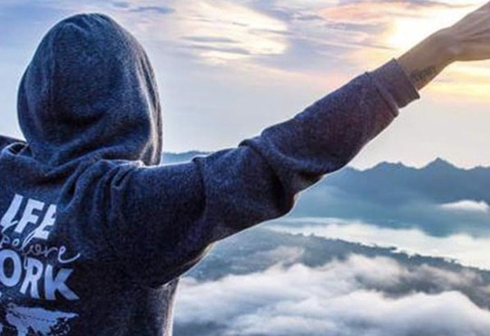 Female solo traveller with arms out at Mount Batur volcano